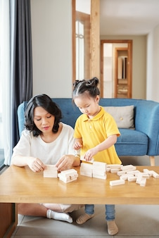 Młoda azjatka i jej córeczka bawią się drewnianymi cegłami i robią mury i wieże