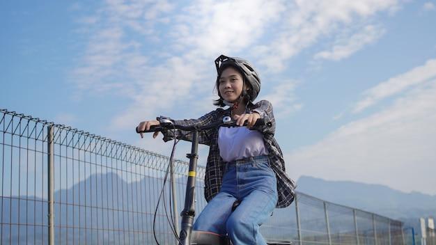 Młoda azjatka jeździ do pracy rowerami, jest szczęśliwa i bezpieczna