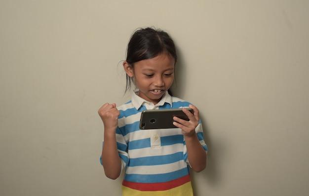 Młoda azjatka korzystająca ze smartfona i patrząca na ekran przerażona z zaskoczeniem na twarzy