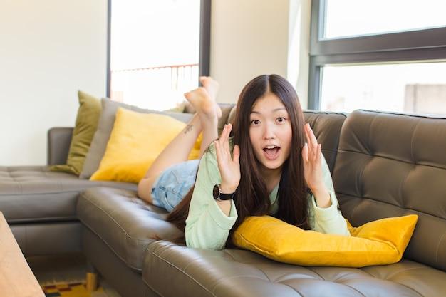 Młoda azjatka krzyczy z rękami do góry, czuje się wściekła, sfrustrowana, zestresowana i zdenerwowana