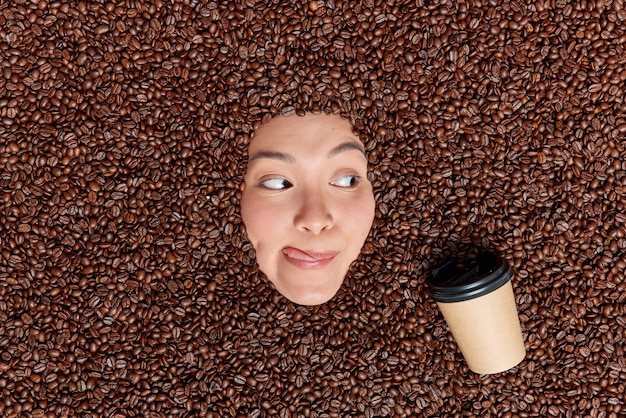 Młoda azjatka, miłośniczka kawy, patrzy na apetyczny kubek orzeźwiającego napoju oblizuje usta językiem otoczonym brązowymi prażonymi nasionami zawierającymi dużą ilość przeciwutleniaczy