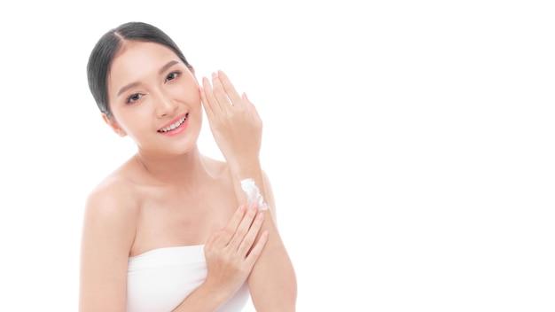 Młoda azjatka nakładająca naturalny krem balsam do ciała na rękę po prysznicu z czystą skórą