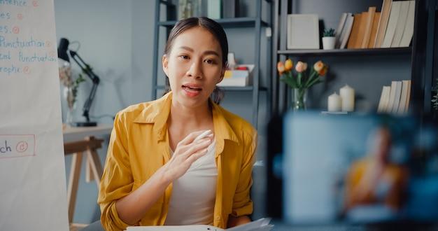 Młoda azjatka nauczycielka angielskiego w wideokonferencji, rozmawiając przez kamerę internetową, uczy się uczyć na czacie online w domu