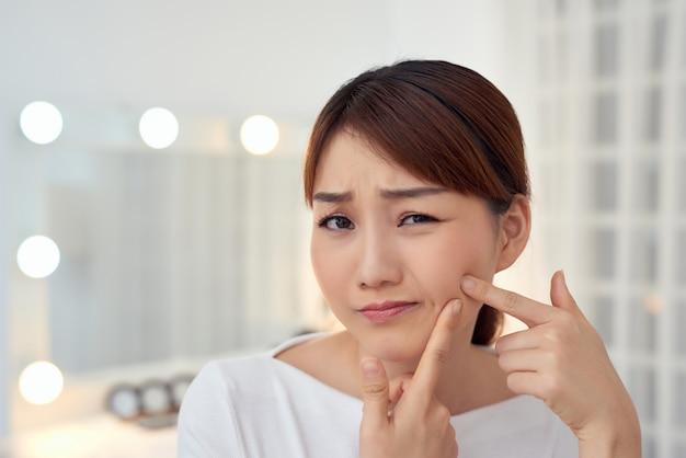 Młoda azjatka nieszczęśliwa dotyka jej skóry