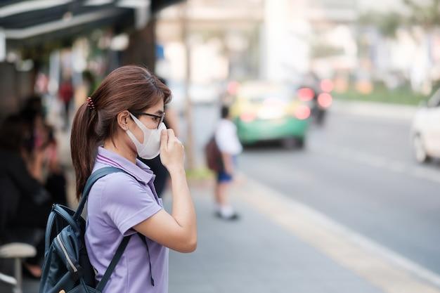 Młoda azjatka nosząca maskę oddechową n95 chroni i filtruje pm2.5 (cząstki stałe) przed ruchem ulicznym i pyłem. pojęcie opieki zdrowotnej i zanieczyszczenia powietrza