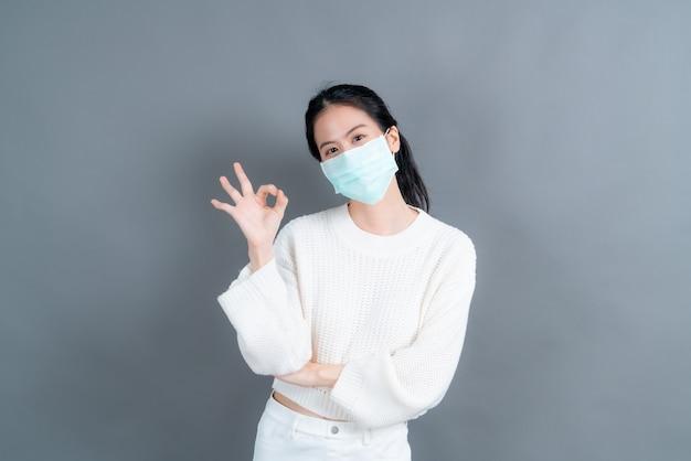 Młoda azjatka nosząca medyczną maskę na twarz chroni przed pyłem z filtra pm2,5, przeciw zanieczyszczeniom, antysmogowi, covid-19 i pokazuje znak ok