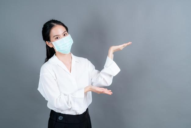 Młoda azjatka nosząca medyczną maskę na twarz chroni przed pyłem z filtra pm2,5, przeciw zanieczyszczeniom, antysmogowi i covid-19 z ręką prezentowaną na boku