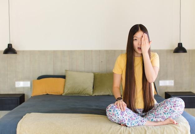 Młoda azjatka obejmująca jedno oko, siedząca na łóżku