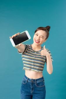 Młoda azjatka pokazuje kciuk w górę z telefonem komórkowym