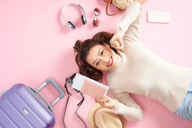 Młoda azjatka pokazuje swój paszport, leżąc na różowej podłodze z bagażem podróżnym dookoła