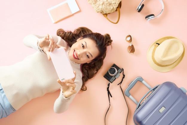 Młoda azjatka pokazuje swojego smartfona leżąc na różowej podłodze z otaczającym bagażem podróżnym