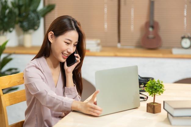 Młoda azjatka pracująca z laptopem i używająca smartfona rozmawiającego o biznesie w domu