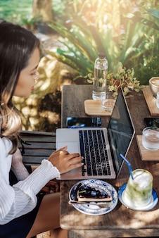 Młoda azjatka pracuje na swoim nowoczesnym laptopie, siedząc przy stole, gdzie jest ciasto i koktajl.