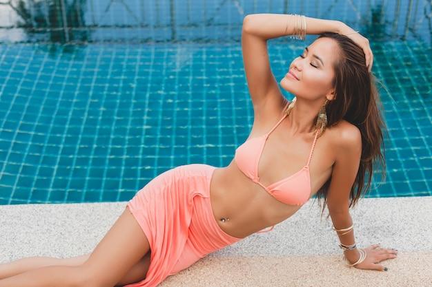 Młoda azjatka seksowna piękna kobieta w różowym bikini, leżąc na basenie, szczupła, opalona skóra, akcesoria glamour, bransoletki, zrelaksowany, uśmiechnięty, zmysłowy, letnie wakacje, nogi