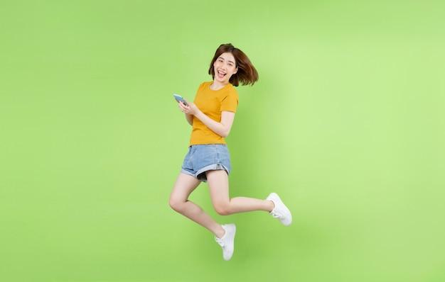 Młoda azjatka skacze na zielonym tle
