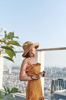 Młoda azjatka stojąca na dachu i używająca aparatu do robienia zdjęć