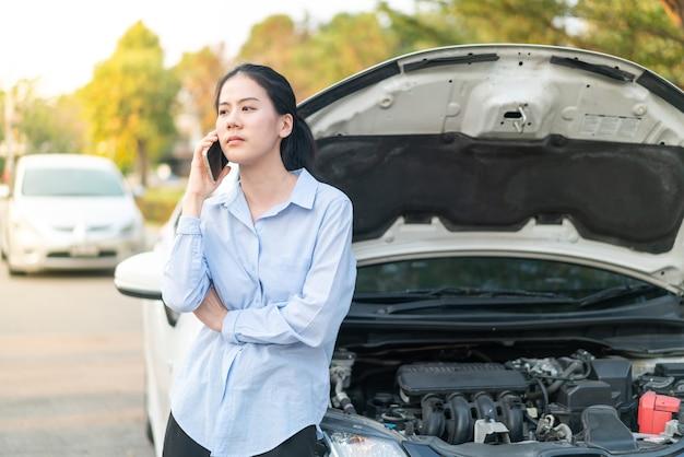 Młoda azjatka stojąca w pobliżu zepsutego samochodu z wyskakującym kapturem, mająca problemy z pojazdem