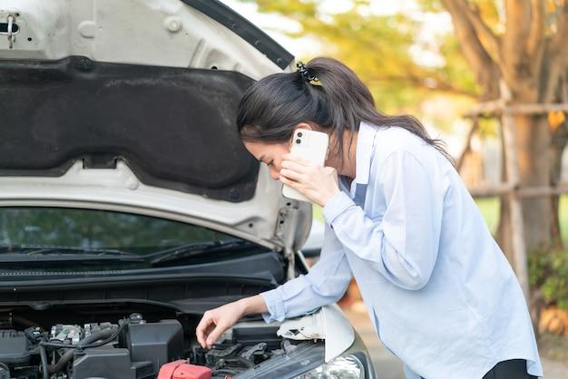 Młoda azjatka stojąca w pobliżu zepsutego samochodu z wyskakującym kapturem, mająca problemy ze swoim pojazdem