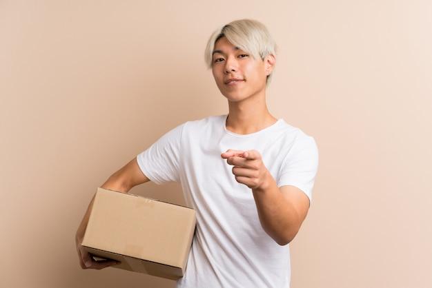Młoda azjatka trzyma pudełko, aby przenieść je na inne miejsce, wskazując jednocześnie na przód