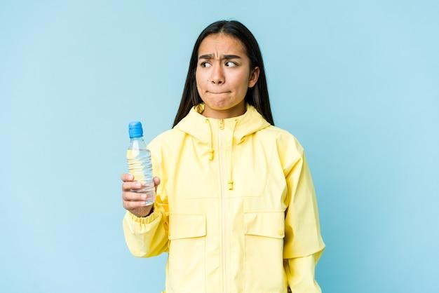 Młoda azjatka trzymająca butelkę wody na niebieskiej ścianie jest zdezorientowana, wątpliwa i niepewna.