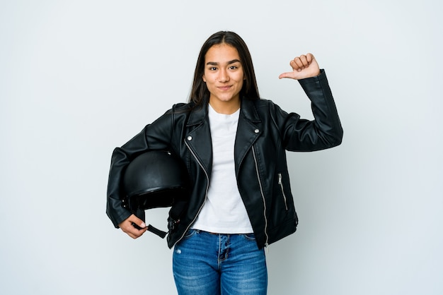 Młoda azjatka trzymająca kask motocyklowy nad odizolowaną ścianą czuje się dumna i pewna siebie, przykład do naśladowania.