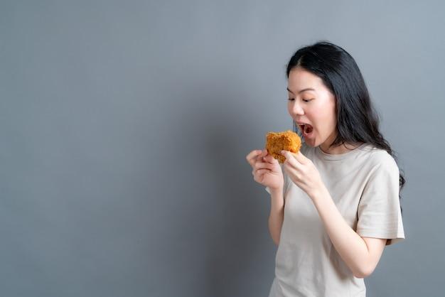 Młoda azjatka ubrana w t-shirt z radosną buzią i ciesząca się jedzeniem smażonego kurczaka na szarej ścianie