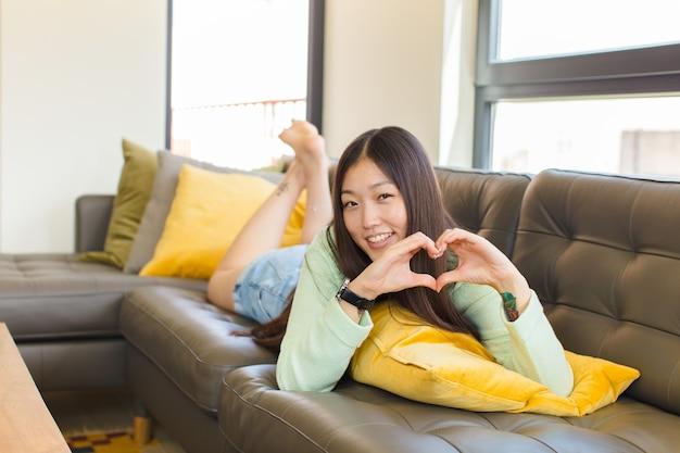 Młoda azjatka uśmiecha się i czuje się szczęśliwa, słodka, romantyczna i zakochana, tworząc kształt serca obiema rękami