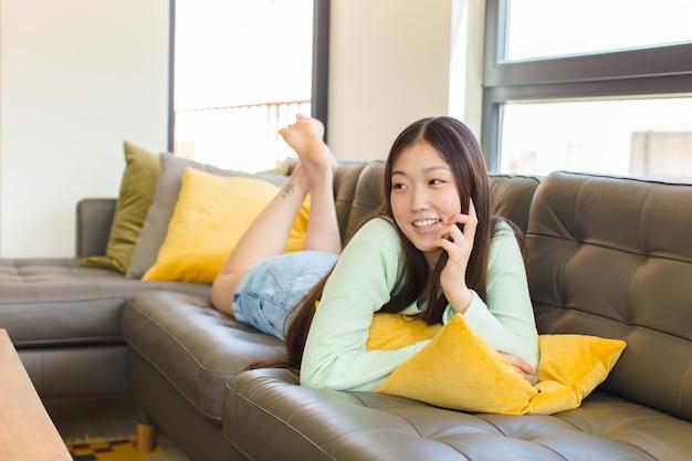 Młoda azjatka uśmiecha się radośnie i marzy lub wątpi, patrząc w bok