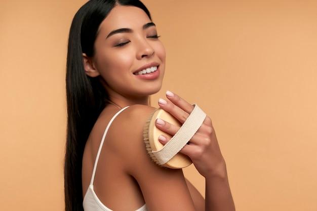 Młoda azjatka w białej bieliźnie i czystej, promiennej skórze wykonuje masaż antycellulitowy suchym pędzlem na beż
