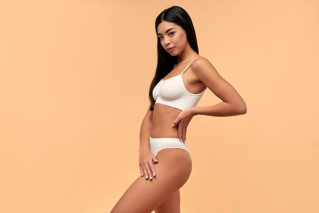 Młoda azjatka w białej bieliźnie o stonowanej sylwetce i smukłej sylwetce na beżowym tle. laserowe usuwanie włosów. operacja plastyczna