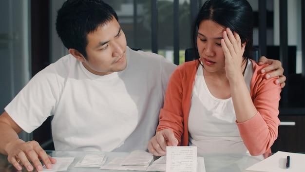 Młoda azjatka w ciąży rejestruje dochody i wydatki w domu. mama zmartwiona, poważna, stresująca podczas rekordowego budżetu, podatków, dokumentów finansowych pracujących w salonie w domu.