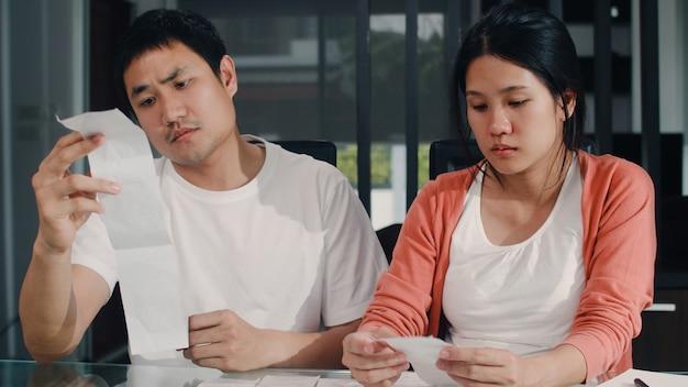 Młoda azjatka w ciąży rejestruje dochody i wydatki w domu. tata zmartwiony, poważny, stres podczas rekordowego budżetu, podatków, dokumentów finansowych pracujących w salonie w domu.