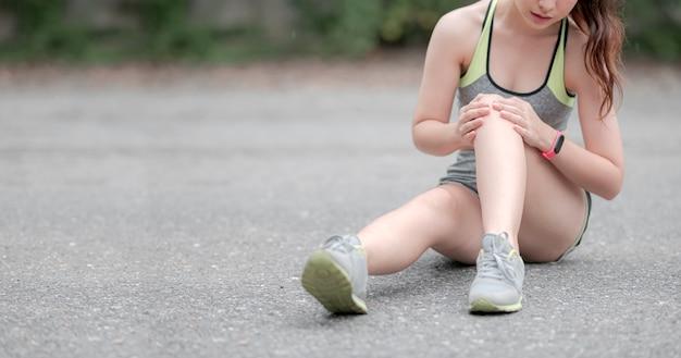 Młoda azjatka w odzieży sportowej siedzi na podłodze, boli kolano podczas biegania na świeżym powietrzu w parku, kopia przestrzeń.