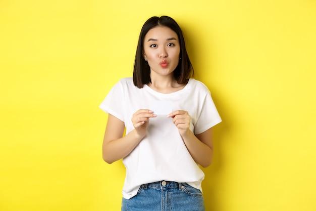 Młoda azjatka w przypadkowej białej koszulce pokazująca plastikową kartę kredytową i zmarszczone usta, idąca na zakupy, żółta.