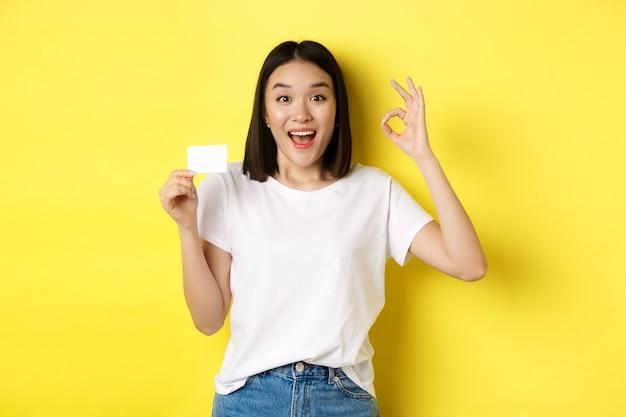 Młoda azjatka w przypadkowej białej koszulce pokazującej plastikową kartę kredytową i w porządku gest, poleca bank, uśmiechając się do kamery, żółty.