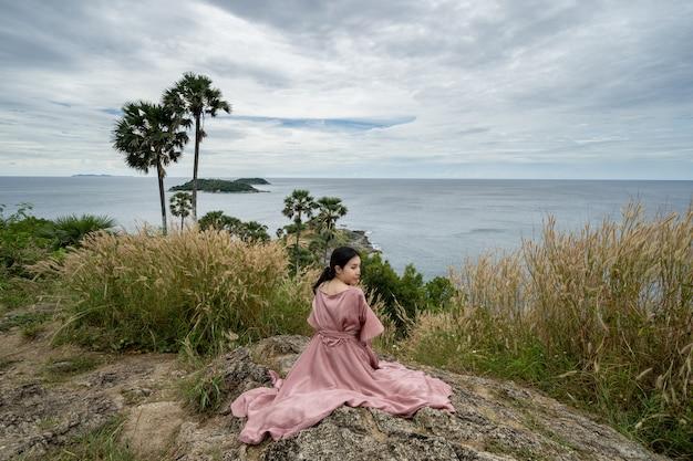 Młoda azjatka w różowej sukience cieszyć się i zrelaksować w punkcie widokowym promthep cape landmark w phuket