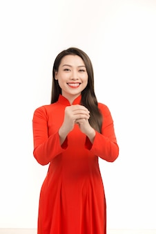 Młoda azjatka w tradycyjnej sukience ao dai, uśmiechnięta i pozdrawiająca, świętująca nowy rok księżycowy lub festiwal wiosny