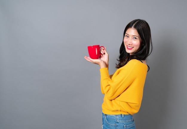 Młoda azjatka w żółtym swetrze trzyma czerwoną filiżankę kawy, dobrze pachnie i delektuje się kawą na szarej ścianie