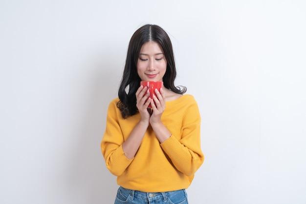 Młoda azjatka w żółtym swetrze trzyma czerwoną filiżankę kawy, dobrze pachnie i delektuje się kawą z białymi