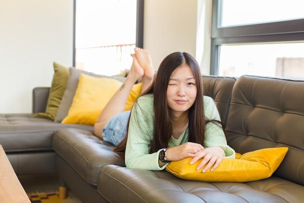 Młoda azjatka wygląda szczęśliwie i przyjaźnie, uśmiechnięta i mrugająca okiem z pozytywnym nastawieniem