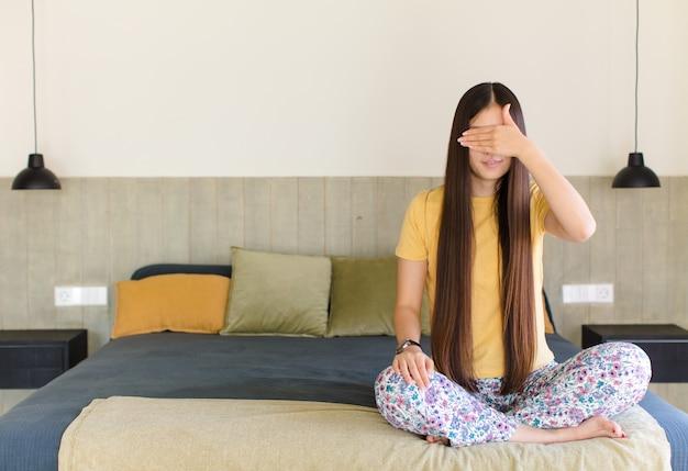 Młoda azjatka wyglądająca na skoncentrowaną i medytującą, czującą się usatysfakcjonowaną i zrelaksowaną, myślącą lub dokonującą wyboru