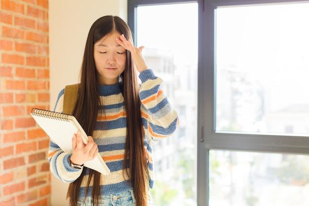 Młoda azjatka wyglądająca na skoncentrowaną, zamyśloną i zainspirowaną, burzy mózgów i wyobraźni z rękami na czole