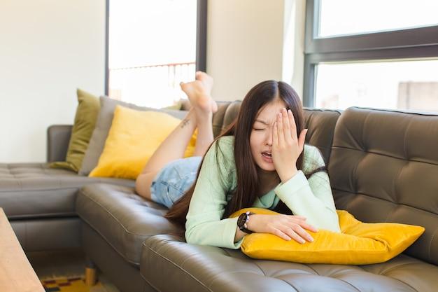 Młoda azjatka wyglądająca na śpiącą, znudzoną i ziewającą, z bólem głowy i jedną ręką zakrywającą połowę twarzy