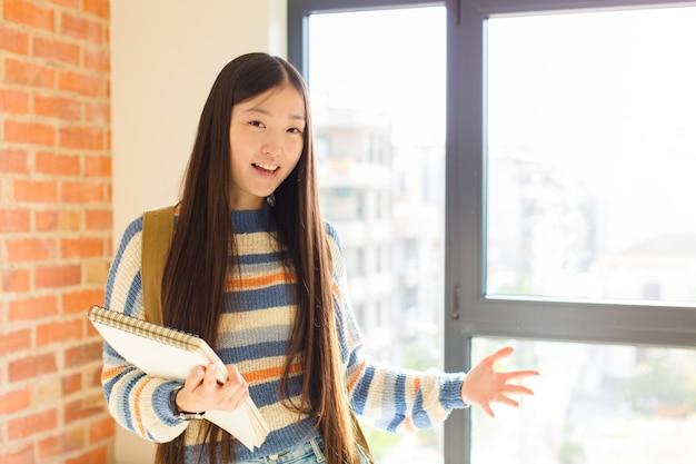 Młoda azjatka wyglądająca na szczęśliwą, arogancką, dumną i zadowoloną z siebie, czując się jak numer jeden