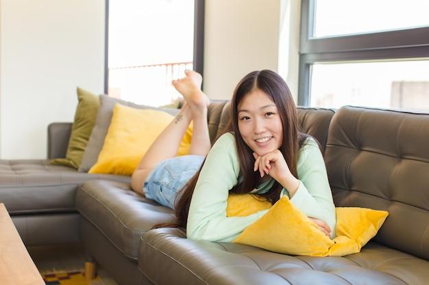 Młoda azjatka wyglądająca na szczęśliwą i uśmiechniętą z ręką na brodzie, zastanawiająca się lub zadająca pytanie, porównująca opcje