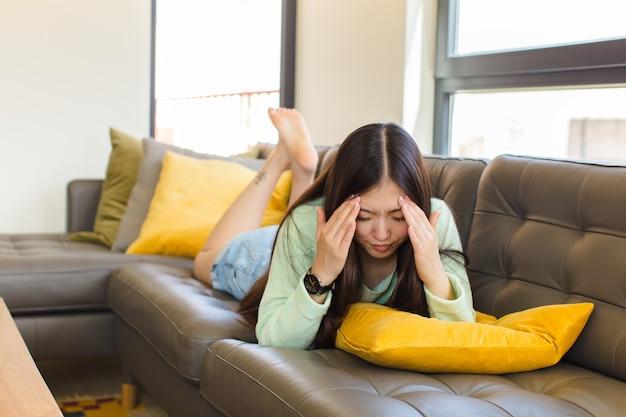 Młoda azjatka wyglądająca na zestresowaną i sfrustrowaną, pracująca pod presją z bólem głowy i zmartwiona problemami