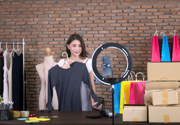 Młoda azjatka z azji na żywo na sprzedaż modnych ubrań jest blogerką prezentującą produkty społecznościowe. jest wpływową postacią w mediach społecznościowych online.