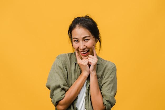 Młoda azjatka z pozytywnym wyrazem twarzy, uśmiechnięta szeroko, ubrana w luźne ubranie na żółtej ścianie. szczęśliwa urocza zadowolona kobieta raduje się sukcesem. koncepcja wyraz twarzy.