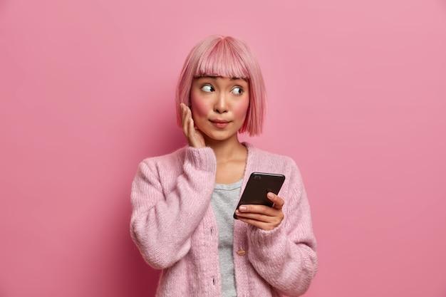 Młoda azjatka z zaskoczonym wyrazem twarzy spogląda na bok, ubrana w zwykły strój, trzyma telefon komórkowy, surfuje po mediach społecznościowych, wysyła treści, udostępnia multimedia online,
