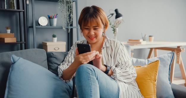 Młoda azjatka za pomocą wiadomości tekstowej na smartfonie lub sprawdź media społecznościowe na kanapie w salonie w domu